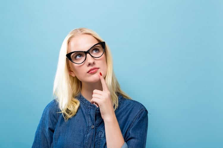 A young, bespectacled woman, wondering how to tell if you have a UTI or an STD.