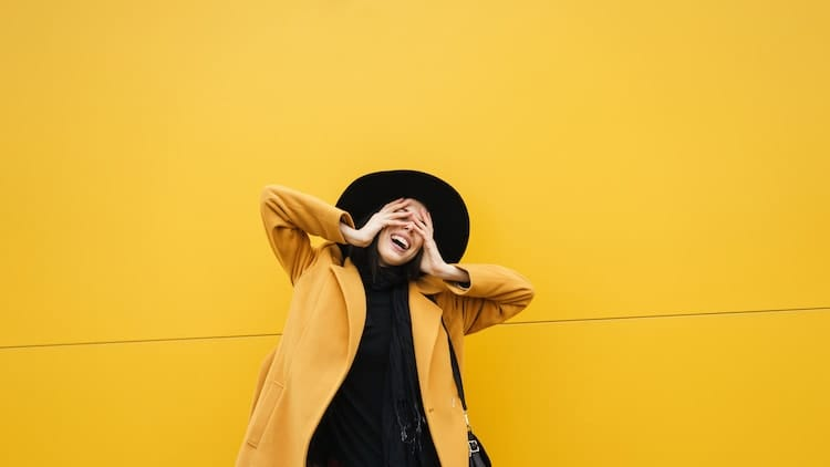 A young and stylish woman against a yellow background, shy about asking getting STD tested while on her period.