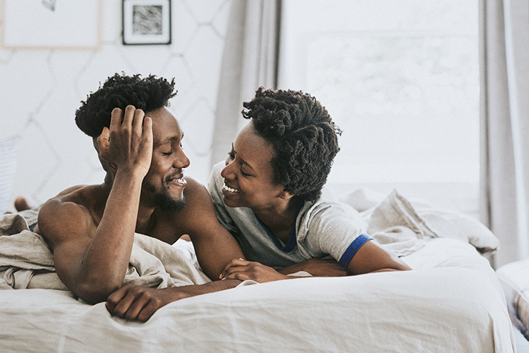 Black couple in bed, looking at one another with love.