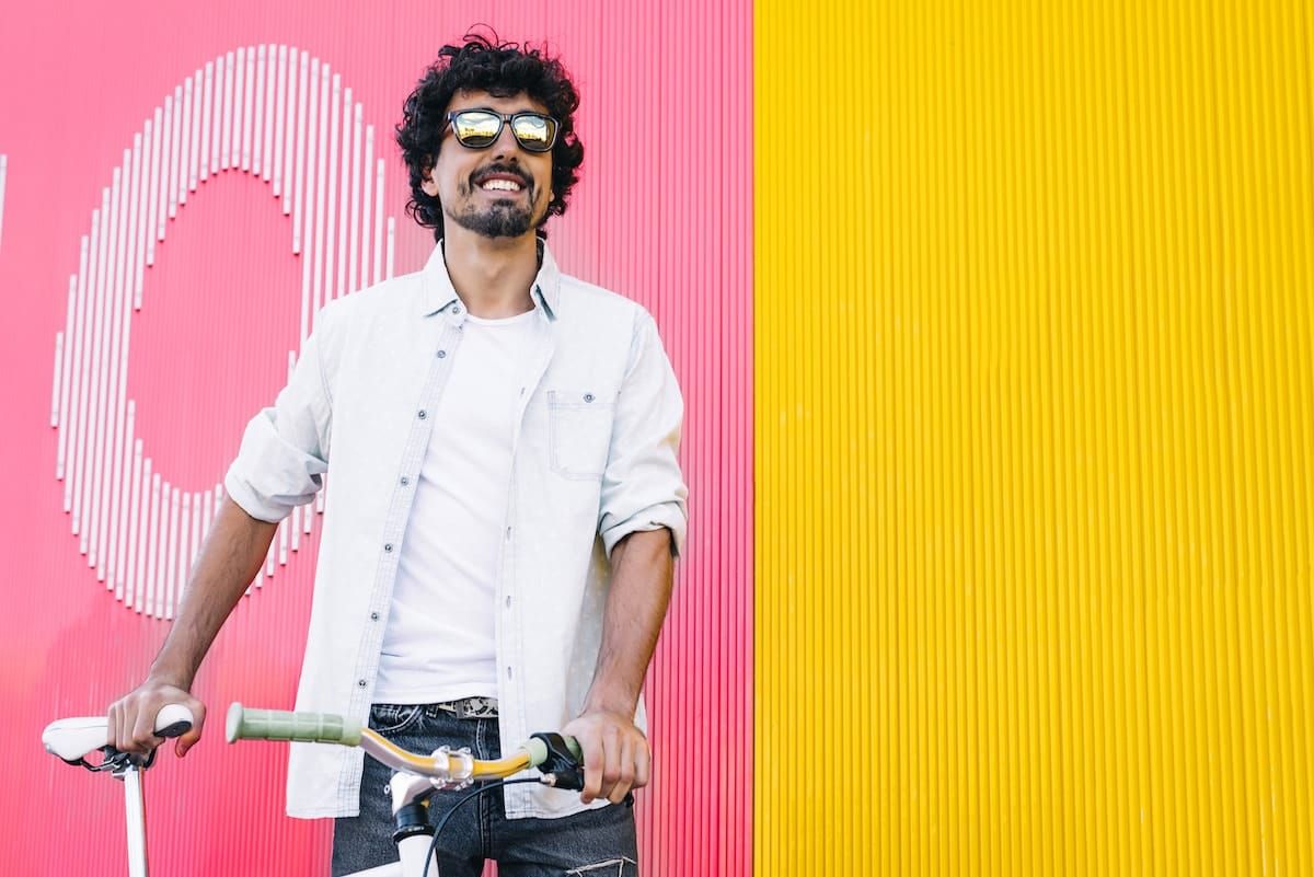 A man smiling, wearing sunglasses and holding on to a bicycling, standing in front of a brightly colored wall.