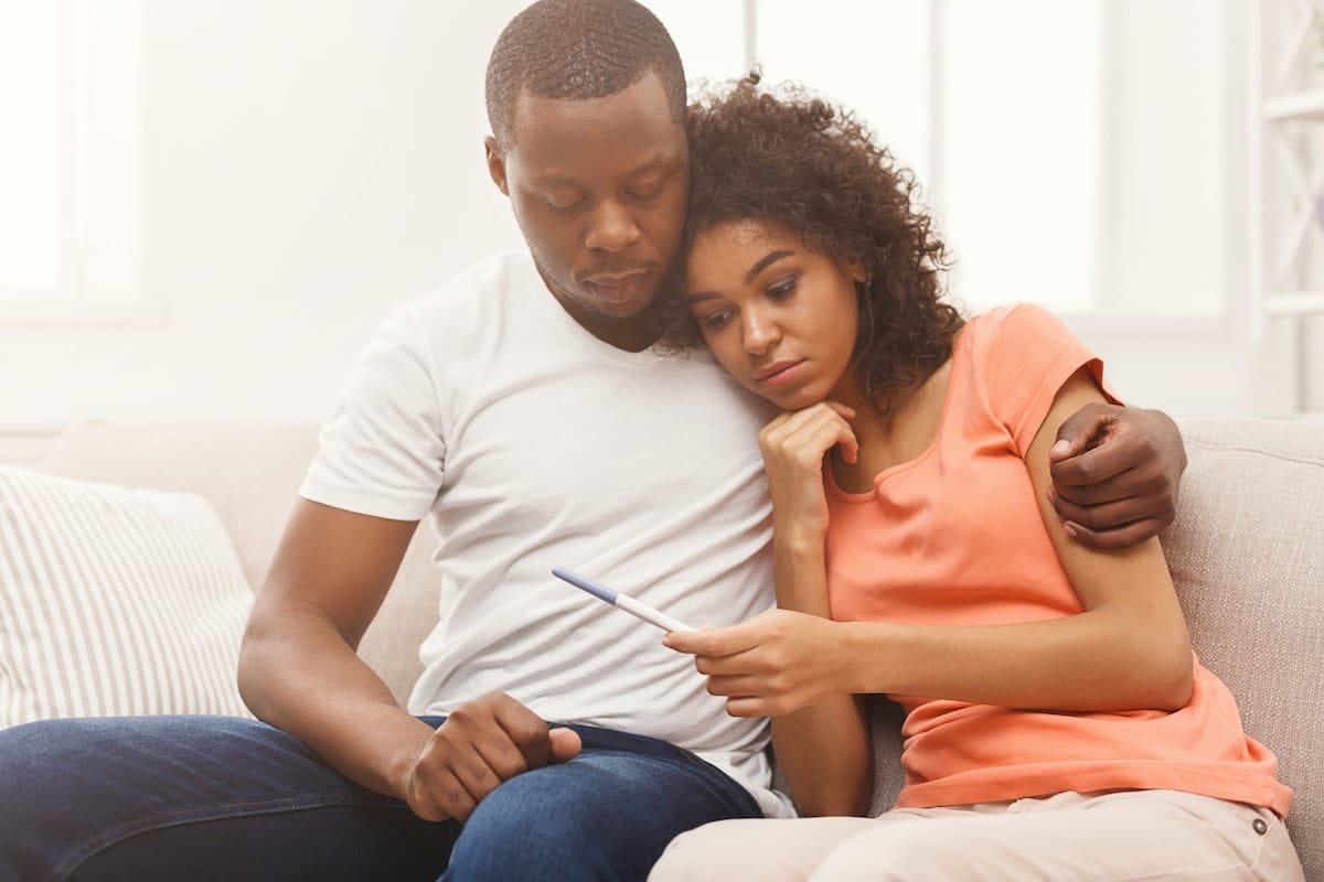 Black couple, seated next to one another on the couch, looking concerned at a pregnancy test.
