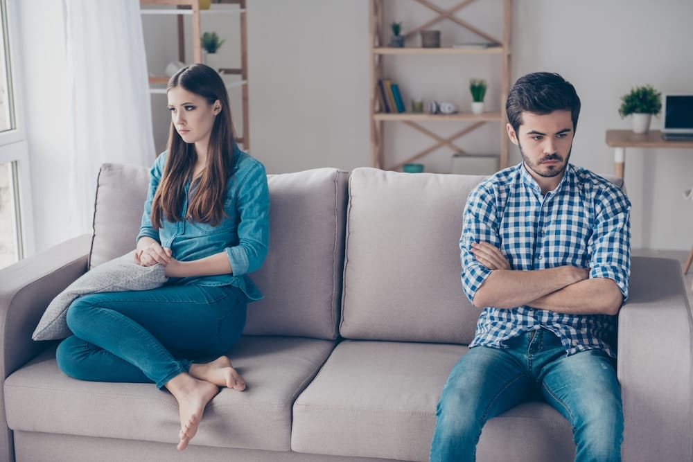 Annoyed couple is ignoring each other, sitting on the couch