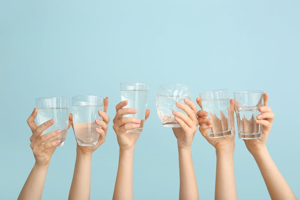Female hands with glasses of water