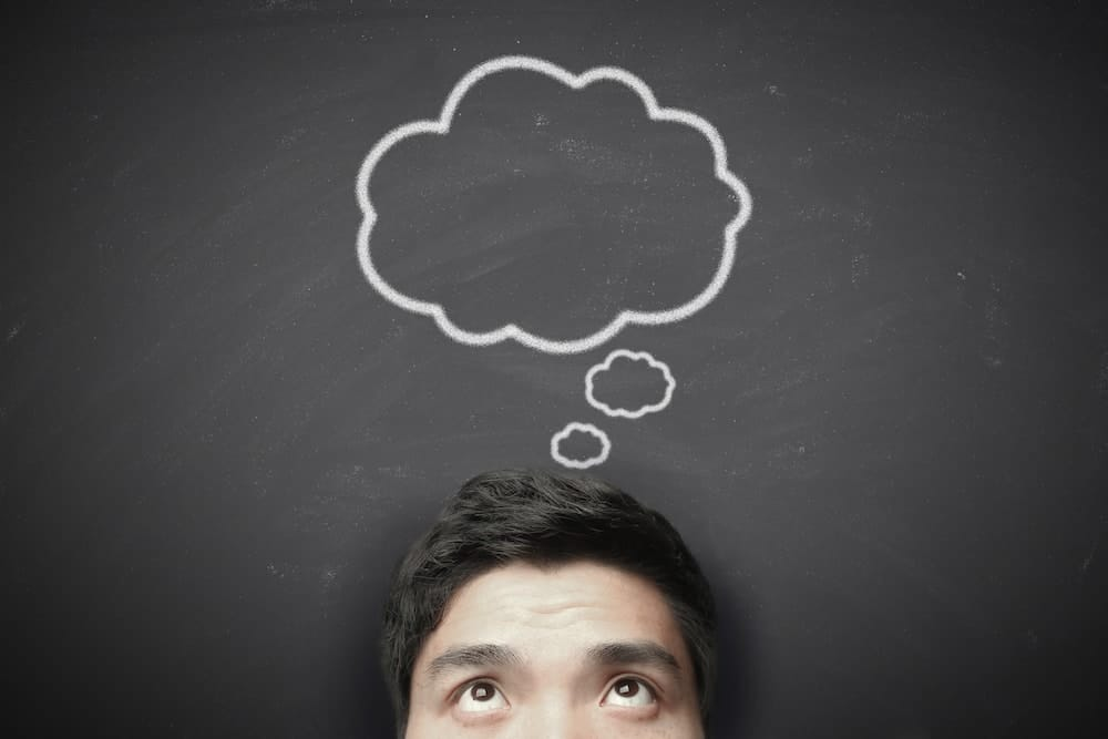 Thinking man with thinking bubble on blackboard