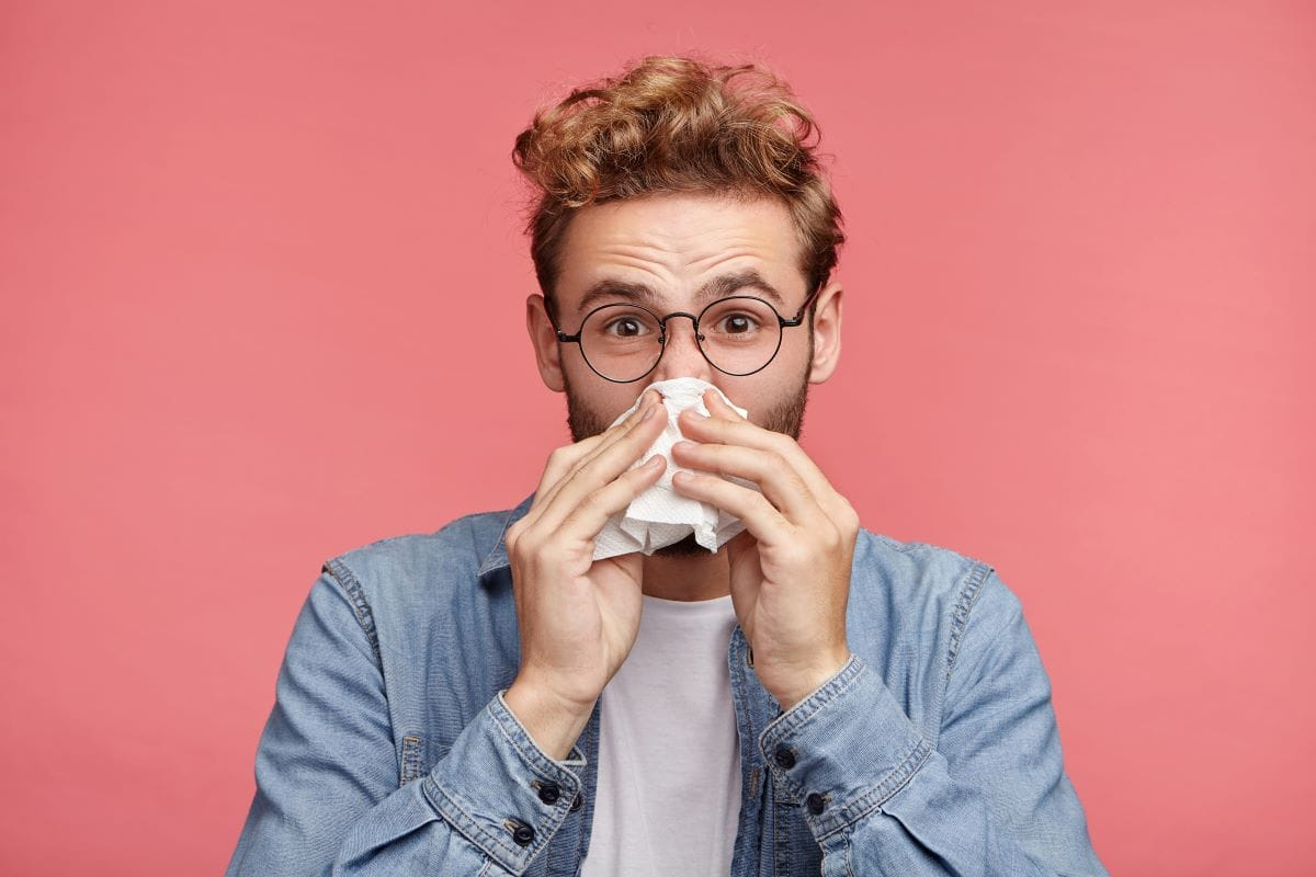 bearded man has running nose, rubs nose with handkerchief