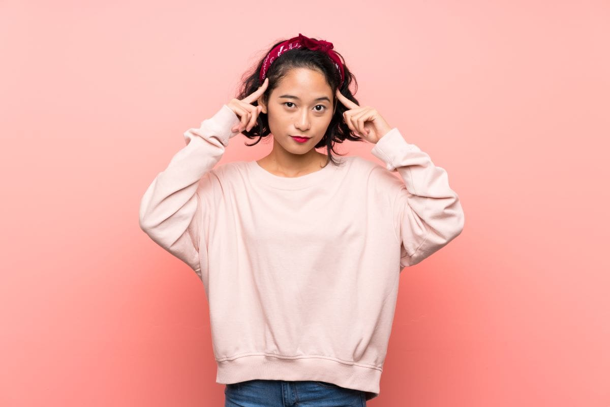 Asian young woman over isolated pink background having doubts and thinking