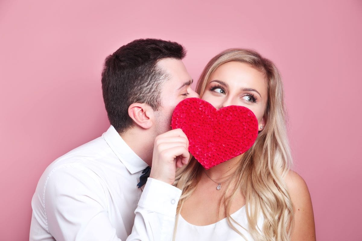 Young couple holding red love heart over eyes and kissing