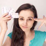 woman holding three packs of birth control pills